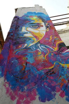 A stencil graffiti art work by urban street artist C215 of a colorful and expressive face
