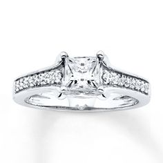 Simply elegant, this engagement ring features a fiery princess-cut diamond center, with round diamonds lining the 14K white gold band. The ring has a total diamond weight of 7/8 carat. Diamond Total Carat Weight may range from .83 - .94 carats.