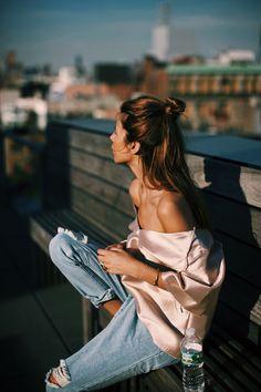 Un jean boyfriend destroy twisté avec une blouse en satin rose poudré col bardot pour gagner en féminité.