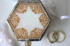 Glass ring holder with a gold wedding ring pillow