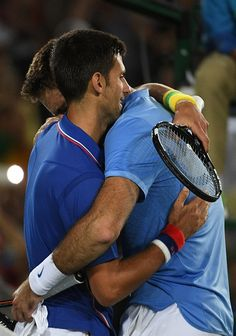 Argentina's Juan Martin del Potro hugs Serbia's Novak Djokovic after winning their men's first round singles tennis match at the Olympic…