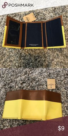 NWT American Eagle Trifold Wallet Brand new wallet! Dark blue and brown inside and yellow and brown outside- has a vintage look to the outside. Reasonable offers accepted. Bundle for a private discount! American Eagle Outfitters Bags Wallets