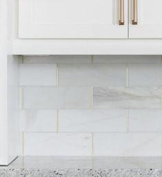 A marble tile backsplash with shimmering brass strips.