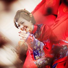 Red silk features heavily in this bride's wedding garb, a traditional bell sleeve two-piece gown with a Mandarin collar called a qun kwa.