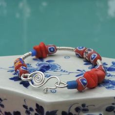 Coral Reef Garden Bracelet with opaque red-orange sea glass from Seaham, England, recycled glass beads from Ghana and Argentium Silver.