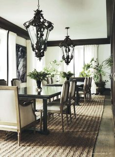 White dining room with black painted trim and crown molding. Two dining tables, large lanterns