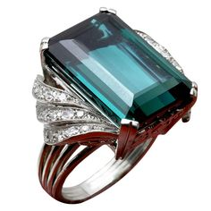Emerald Cut Teal Green Tourmaline Ring with Diamond Accents in the syle of H. Stern. The mounting is platinum and features a gorgeous 21.78 carat tourmaline measuring 19.46 x 13.55 x 9.44 mm VVS clarity and 34 single cut diamonds totaling approximately 0.75 ct. E-F color, VS1 clarity. Late 1950s. Judging by the other pictures of this piece, that red is merely shadow.