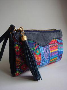 Bolsa feita de couro ecológico e a frente feita de tecido de algodão quiltada em manta acrílica. Possui 3 divisões: 2 bolsos com zíperes e uma divisória com fechamento com botões. Duas alças: uma de pulso e outra transversal.