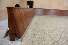 Stained wood boards around and indoor arena. If you look closely you can see the mechanism for a sliding door/gate.