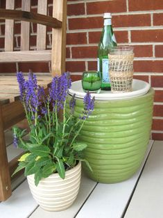 Little side table for garden seating area made with a large planter and a terra cotta saucer that was sealed, painted and turned into a tabletop. Now there's a spot for a book, a little drinky-drink, or even a plate full of bbq.