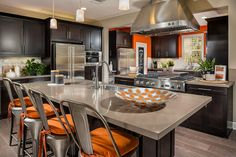 A stunning stainless steel range hood and orange accents define this kitchen. Plan 3CR, a new home by Pardee Homes at Casabella. San Diego, CA.