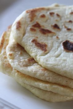 My favorite Naan recipe! 1/2 cup warm water 2 teaspoons active dry yeast 1 teaspoon sugar 1/2 teaspoon salt 2 1/2 cups all purpose flour, plus extra for dusting and rolling 1/4 cup oil (I've used both canola and olive oil with good results) 1/3 cup plain yogurt 1 egg, beaten oil or ghee, for frying  *ghee is clarified butter