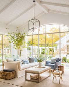 Family room with Belgian linen sofas and chambray blue accents, over size steel windows, and French and Swedish antiques in traditional modern farmhouse in California by Steve and Brooke Giannetti in C Magazine