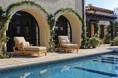 Spanish Mediterranean revival. love the plants on the arches around the pool.