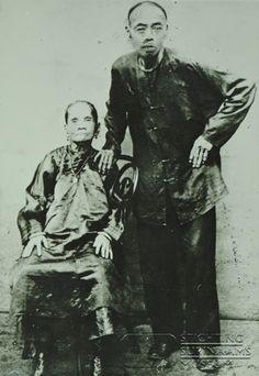Portret immigranten echtpaar uit China. De heer Kwan-Paw Tjon; geb. 1836 te Wijtjoe, China; overl. 1909 te Commewijne, Suriname. Mevrouw A_Thai Shi; geb. 1849 te Wijtjoe, China; overl. 1910 te Commewijne, Suriname. Dit echtpaar arriveerde in maart 1866 in Suriname.  Geboren uit dit huwelijk de volgende vier kinderen: 1. Anna L.J. A-Loi Tjon Kwan Paw, 1876-1940; 2. Stephanus Soei-Loi Tjon Kwan Paw, 1880-1958; 3. Johannes A-Loi Tjon Kwan Paw, 1882-1921; 4. Maria Sie-Moi Tjon Kwan Paw…
