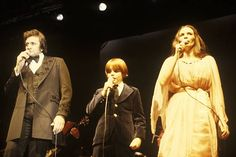 Johnny Cash performing on stage with wife June Carter Cash and their son John Carter Cash
