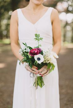 A white-and-purple posy comprised of anemones, roses, lily of the valley, and greenery by @greendandelion | Brides.com
