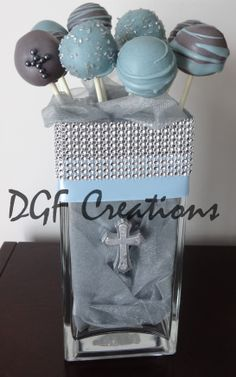 Grey and Blue-grey cake pops filled with organza and decorated with blue and diamond ribbon, with a little silver cross in the middle for centerpieces.