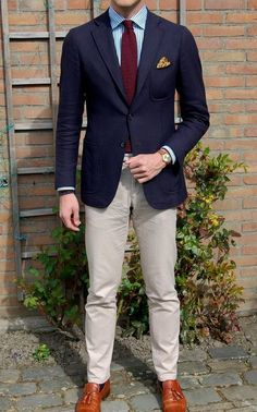 Shop this look on Lookastic: https://lookastic.com/men/looks/blazer-dress-shirt-chinos/14462 — White and Blue Vertical Striped Dress Shirt — Burgundy Knit Tie — Yellow Floral Pocket Square — Navy Wool Blazer — Brown Leather Watch — Beige Chinos — Tobacco Leather Tassel Loafers