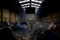Tents inside a warehouse in 'The Jungle,' the camp where hundreds of migrants are living in Calais, France, from where they try to cross the English Channel to make it to the United Kingdom. Photograph by Mary Turner.