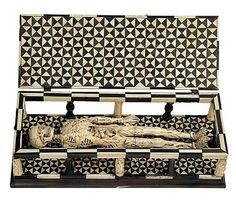 An western Swiss ivory and wood memento mori (Tödlein), c.1520; a skeleton, symbol of death, half-eaten by various creatures, lies within a coffin. (Museum Schnütgen)