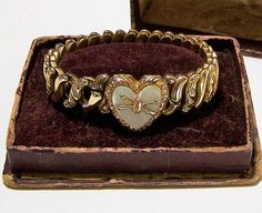 Antique to vintage gold filled expansion bracelet with original box Mother of pearl heart locket attached to an expansion bracelet Box reads Carmen adjustable bracelet, made only by the DF Briggs Co, patented 1890-91 Heart locket is hinged at the top with two small frames inside Decorative alternate links Petite size, although it opens very wide, inside unstretched diameter is 4 3/4, stretched to its largest is 8 1/4. I would recommend this for a petite woman. Includes the original ...