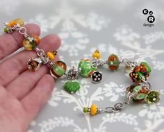 EJR Design is proud to present this unique, one of a kind charm bracelet! Youll notice a distinctive flower theme throughout this lovely piece, possibly reminding you of a sunny springtime day... It was designed and created by me, Elizabeth Ryan, using my own signature glass lampwork beads. These beads were made in my studio using shades of amber* and sage** raw soda-lime glass. The beads were then combined with beautiful, vintage pressed glass beads, Hill Tribe charms, various oxidized…