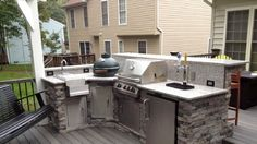 L-shaped stone facade outdoor kichen, with sink, beer dispenser and a Big Green Egg.