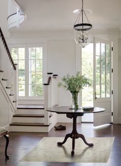 source: Donald Lococo Architects    Traditional entryway with glass paned front door. Oversized Hundi pendant, round pedestal entry table and pale sage rug. Hardwood floors and stairs with white spindles and paneling.