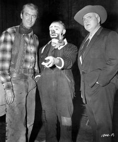 James Stewart and Orson Welles leave temporarily the sets of Night Passage and Man in the Shadow, respectively, to extend best wishes to James Cagney at the start of production on Man of a Thousand Faces