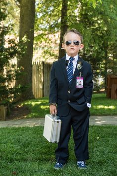 """The ring bearer was dressed to look like a secret service agent. He wore aviator glasses, an earpiece and a badge that read """"Ring Security."""" Instead of carrying a pillow with the rings, he carried a silver metal briefcase for top-notch security."""