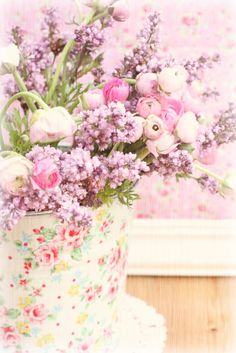Pink and purple flowers in a shabby chic container