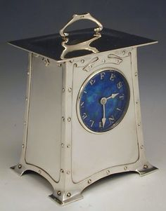 U.K. Silver Arts & Crafts clock with enamel on silver dial, c.1900. Faux rivet decoration to front and sides with carriage clock handle to roof. The clock face with the legend 'FESTINE LENTE' which translates as 'make haste, slowly' // Attributed to Archibald Knox for Liberty's