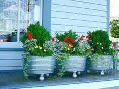 galvanized tubs from tractor supply with red plants from Home Depot at entrance and on patio.