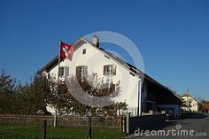 Photo about A classic image of a white Farm House in Switzerland with large roof and the Swiss flag flying outside. Image of white, switzerland, roof - 104525932 Flies Outside, Swiss Flag, Classic Image, White Farmhouse, Farm House, Switzerland, The Outsiders, Stock Photos, Mansions