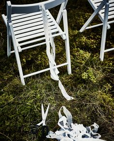 Síť SOLIG rozstříhaná na proužky, připevněná na zadní stranu bílé skládací židle.