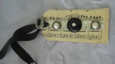 Tag with vintage sheet music, lace,pearl and silver buttons  OR  use sheet music from wedding song as name placard/table number for reception tables