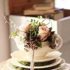 teacups with flowers in them all around the tables. Also put vintage tea pots with more flowers in them mixed in