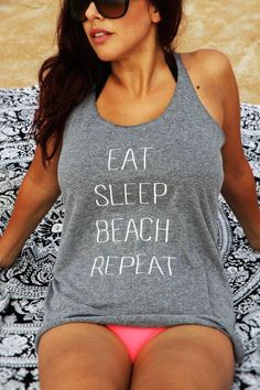 """Lounge on the beach with a heather gray women's very soft and comfortable racer back tank with a white """"Eat Sleep Beach Repeat"""" print. Printed on 50% polyester/25% combed ring-spun cotton/25% rayon, 3"""
