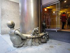 In 2000, Tom Otterness was commissioned to add some little men to the Hilton Times Square's north and south entrances in a sculptural group called Time and Money Creatures in funny hats dangle over clocks, Buddha-like being sits and meditates, two large policemen hold up the metal beam, and figures handle oversized monetary pieces. Meanwhile, on the 41st Street antrance, Male Tourist and Female Tourist look up at one of the clocks from below, the man holding tight to their luggage, the woman…