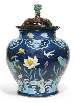 A LARGE FAHUA 'LOTUS AND EGRET' JAR MING DYNASTY, 16TH CENTURY the rounded shoulders tapering to a gently spreading foot, surmounted by a short neck with a lipped rim, boldly decorated in yellow, green, aubergine and turquoise enamel against a dark blue ground, depicting egrets in flight above and wading through a lotus pond, with large blooms and curling leaves, all above crashing waves and rockwork, with a ruyi-filled lotus collar at the shoulder and cloud sprays at the neck, all…