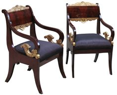 Rare pair of exemplary Russian Empire arm chairs. Mahogany veneered on pine, shoulder boards in book match pattern. Fine detailed gilt wood carvings. Scrolled arms. Padded seats. Rasied on saber legs. Circa 1820.