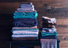 Närbild av en hög med randiga och enfärgade handdukar på en bänk.
