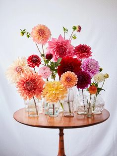 Martha's Flower-Arranging Secrets love the mix of small clear vases and pretty flowers in them (though they will have to be peonies since dahlias aren't in season)