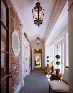 Love the look of the old exposed brick against the grey slate tiles, the french doors (with their gold hardware), and the crisp white millwork