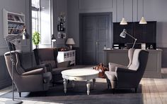 A lounge with grey wing chairs and a white coffee table