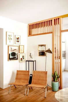 Mid-century, Danish modern living room corner with a potted cactus, gallery wall and sleek rattan chairs.