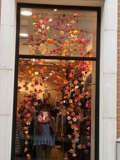Free People window display. It would be fun to do a wall like this inside with branches hanging across with artificial flowers (or some colorful fall leaves) hanging down by string.