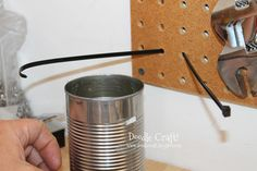 Plastic tie + tin can:  Great idea for cheap peg board organizing.