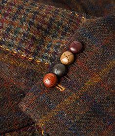 Witziges Detail: Die farblich perfekt abgestimmten, bunten Lederknöpfe an den Manschetten des rostfarbenen, karierten Sakkos aus Harris Tweed.